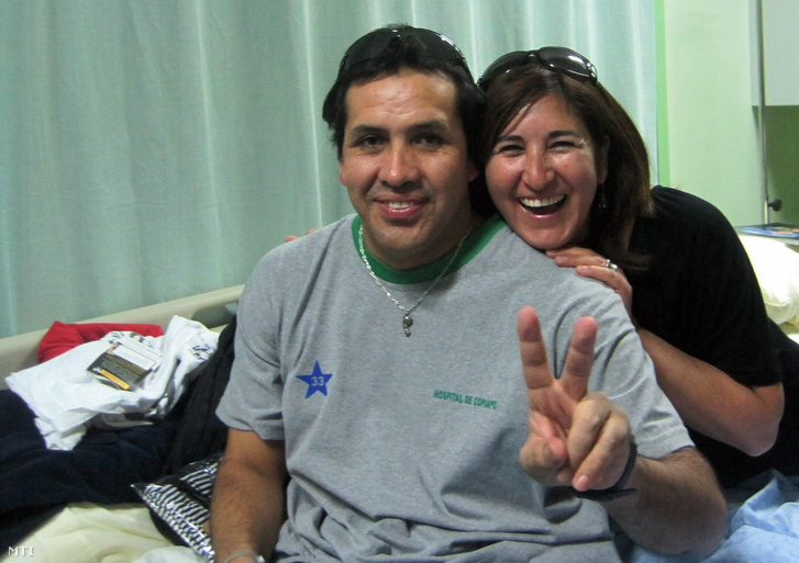 Claudio Acuna chilei bányász a győzelem V-jelét mutatja egyik látogatójának társaságában a copiapói kórházban 2010. október 14-én, miután az előző nap felszínre hozták a közeli San José réz- és aranybányából.