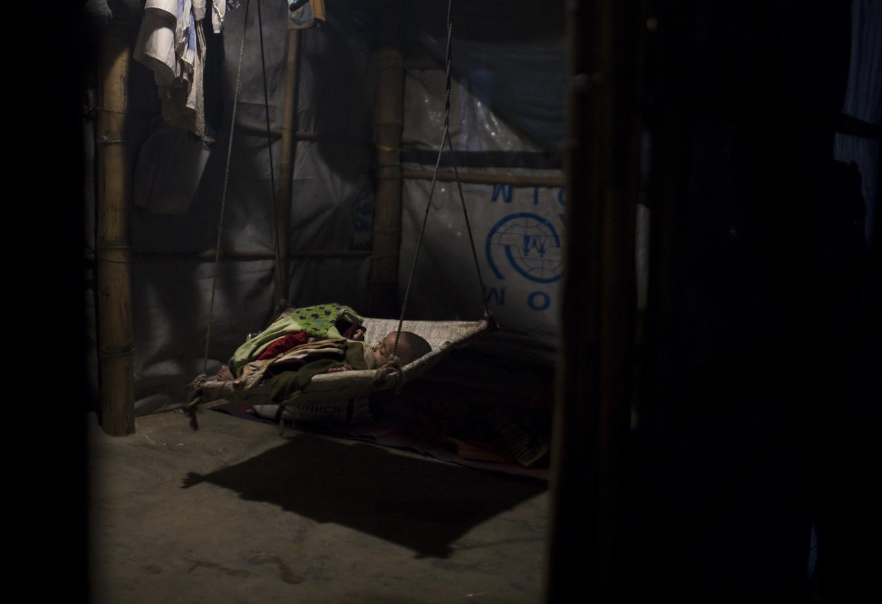 A 2 éves Abad alszik a családi sátorban felállított hintában. Kis területen olyan gyermekek százezrei zsúfolódtak össze rossz higiéniás viszonyok mellett, akik soha, semmilyen oltásban nem részesültek, így teljesen védtelenek a betegségekkel szemben.
