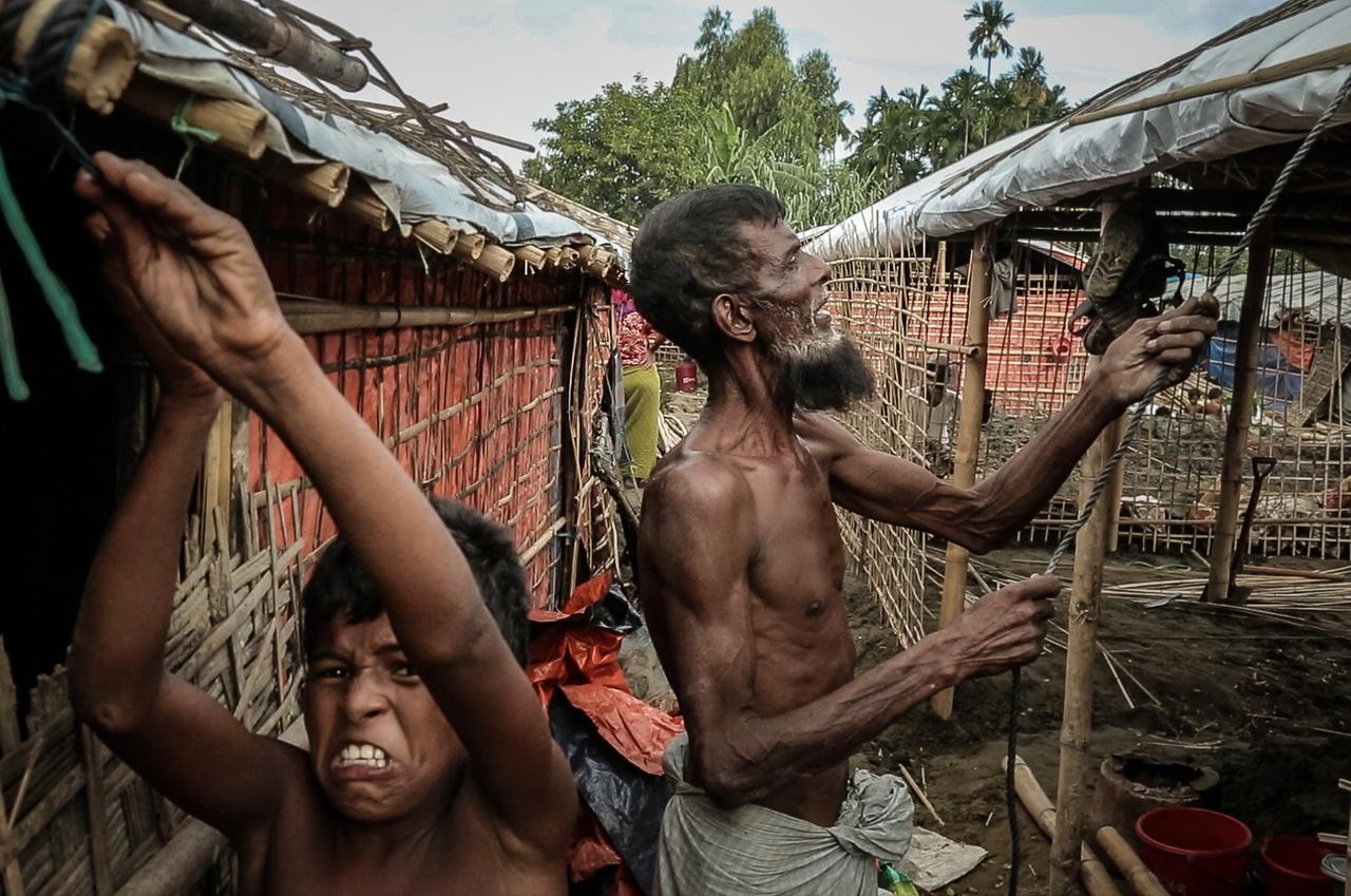 Sátrat épít egy rohginja család a Shamlapur menekülttáborban.