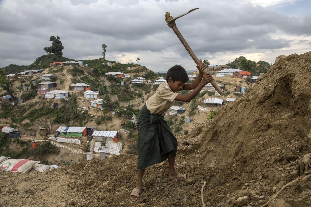 Rohingja fiú ássa a család új sátorhelyét a monszun érkezése előtt június 5-én. A saras domboldalakba épült sátortáborokban gyakoriak a kisebb földcsuszamlások, ilyenkor a sátorokat is könnyen elmoshatja az eső a domboldallal együtt.