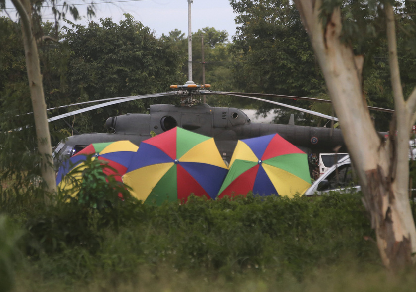 A rendőrök ernyőkkel takarják el a gyerekeket szállító mentőhelikoptereket az észak-thaiföldi Csiangraj tartományban fekvő Maeszaiban.