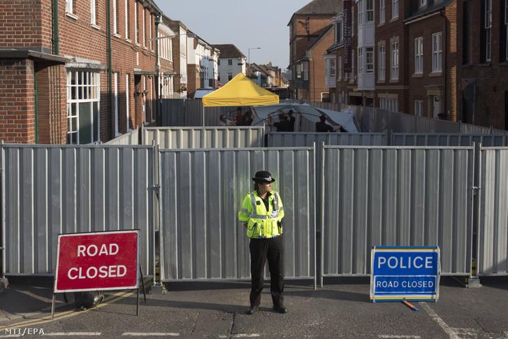 A hajléktalanokat segítő John Baker-háznak otthont adó Rollestone utcát lezáró fémfal előtt őrködik egy rendőr az angliai Salisburyben 2018. július 5-én. A házat azzal kapcsolatban vonták kordon alá, hogy mérgezés miatt rosszul lett egy brit nő és férfi a szomszédos Amesburyben június 30-án.