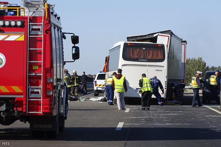 Rendőrök és tűzoltók dolgoznak egy összeroncsolódott busz mellett 2017. október 9-én az M5-ös autópályán Kecskemétnél ahol két teherautó és egy rendőröket szállító busz ütközött össze. A balesetben ketten meghaltak.