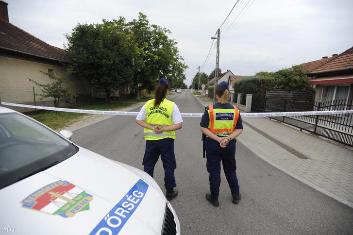 Rendőrök állnak lezárt utcánál Inárcson egy hivatalnál, ahol ügyintézés közben késsel halálosan megsebesített egy hivatali dolgozót egy férfi 2018. július 11-én reggel.