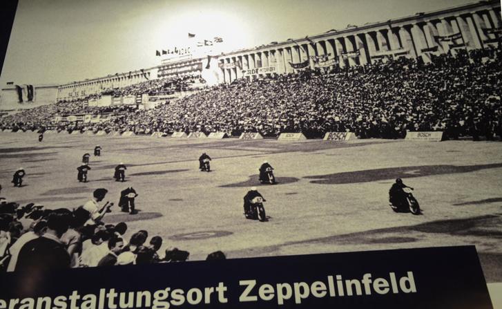 Az első motorversenyek egyike a Zeppelin-tribün előtt. Itt még áll a főtribünhöz két oldalról csatlakozó oszlopsor, amit 1967-ben robbantottak le a tribünről, mivel leromlott állapota miatt közveszélyes lett