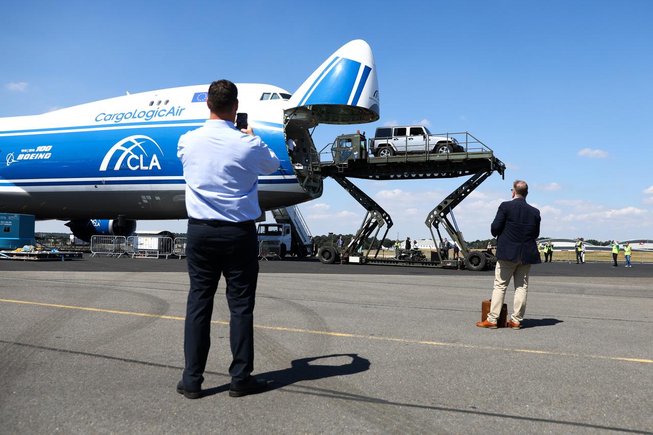 Egy Jeep terepjárót rakodnak a CargoLogicAir Ltd. nevű cég Boeing 747-es szállítógépébe hidraulikus emelőállványról.