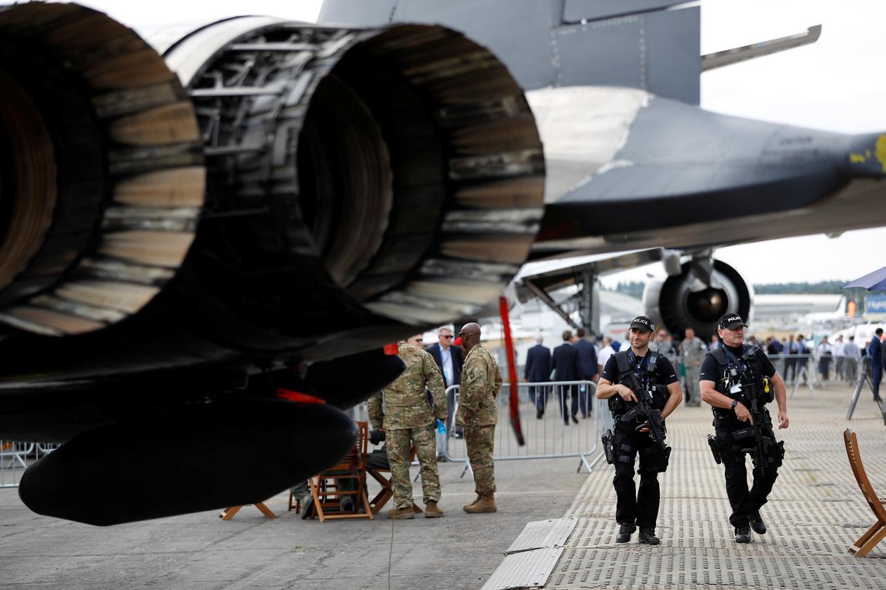 Fegyveres rendőrök járőröznek amerikai katonai gépek között.