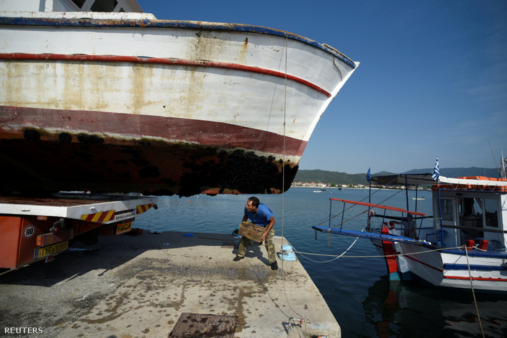 Bontásra váró hajót vizsgál egy halász a faluja kikötőjében