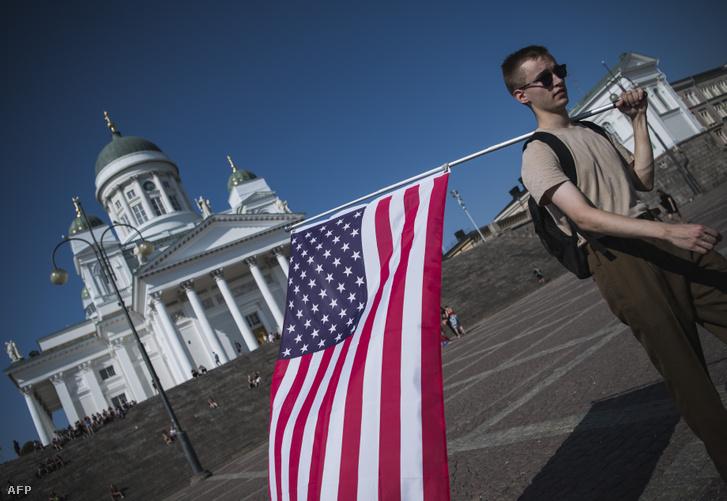 Egy férfi sétál amerikai zászlóval a helsinki elnöki palota közelében ahol az elnöki találkozó zajlott 2018. július 16-án