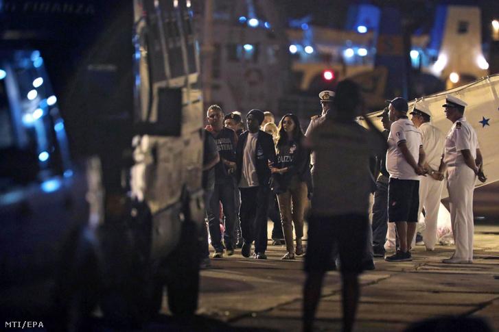 Illegális bevándorlókat kísérnek le a parti őrség tagjai a Diciotti az olasz parti őrség hajójának fedélzetéről a szicíliai Trapani kikötőjébe