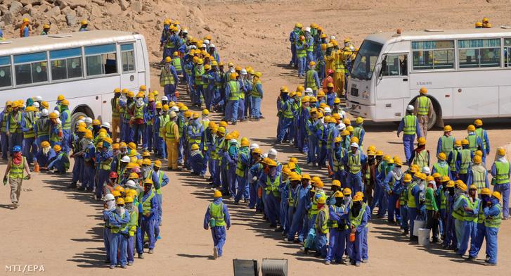 Vendégmunkások sorakoznak a 2022-es katari labdarúgó-világbajnokság egyik épülő stadionjánál Dohában 2013. november 19-én. Az Amnesty International nemzetközi jogvédő szervezet november 17-i közleménye szerint rabszolgaként bánnak a főként Dél-Ázsiából érkező vendégmunkásokkal, rendszeresen nem fizetik ki a bérüket, túlzsúfoltak a munkásszállók, valamint heti hét napot, napi 12 órát dolgoztatják őket a kánikulában.