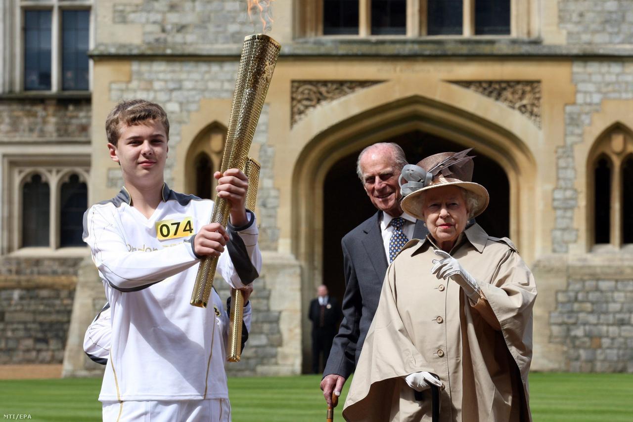II. Erzsébet és Fülöp herceg Phillip Wells 14 éves rögbijátékossal áll a windsori kastély előtt az olimpiai lánggal a 2012-es londoni olimpia kezdete előtt.