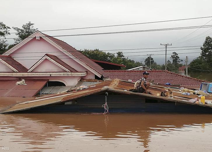 Háztetőn rekedt férfi és kutya a laoszi Attapeu tartományban 2018. július 24-én miután átszakadt a Mekong folyón épített Szepian-Sze Nam Noj erőmű gátja