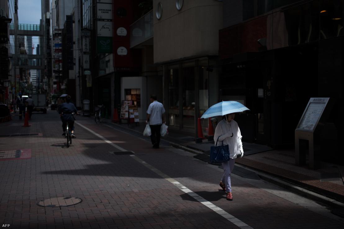 Ventilátor és napernyő a hőség ellen. Tokió, 2018. július 23.