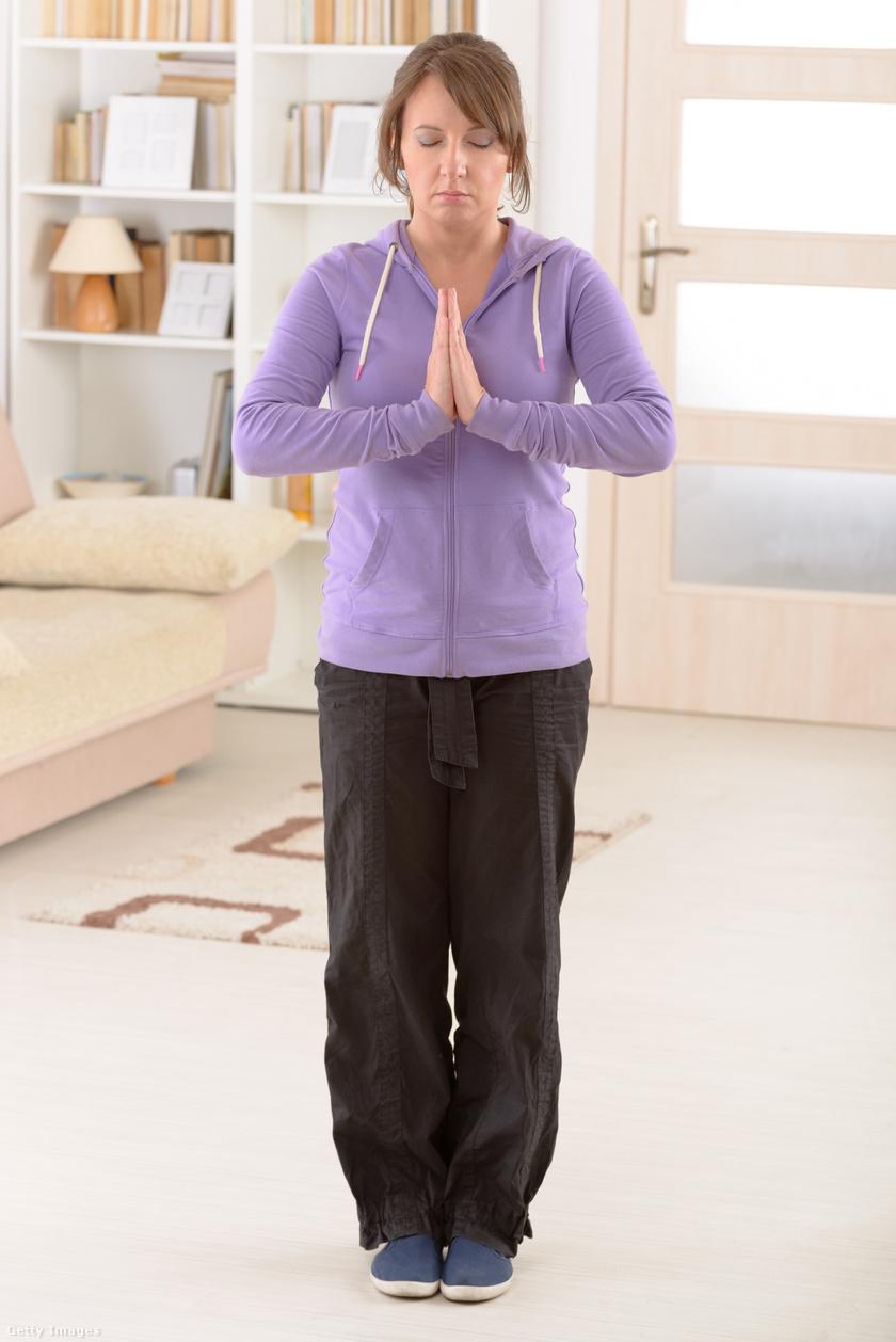 A tai chi lényege, hogy a belső energiáidat mozgósítja. A képen látható pozícióból indulva engedd le a karodat, tárd szét, majd emeld a fejed fölé, mintha hatalmas kört rajzolnál, végül engedd vissza a mellkasod elé, és érintsd össze a tenyeredet. Ezt végezheted vállszéles terpeszben is. Ötször ismételd.