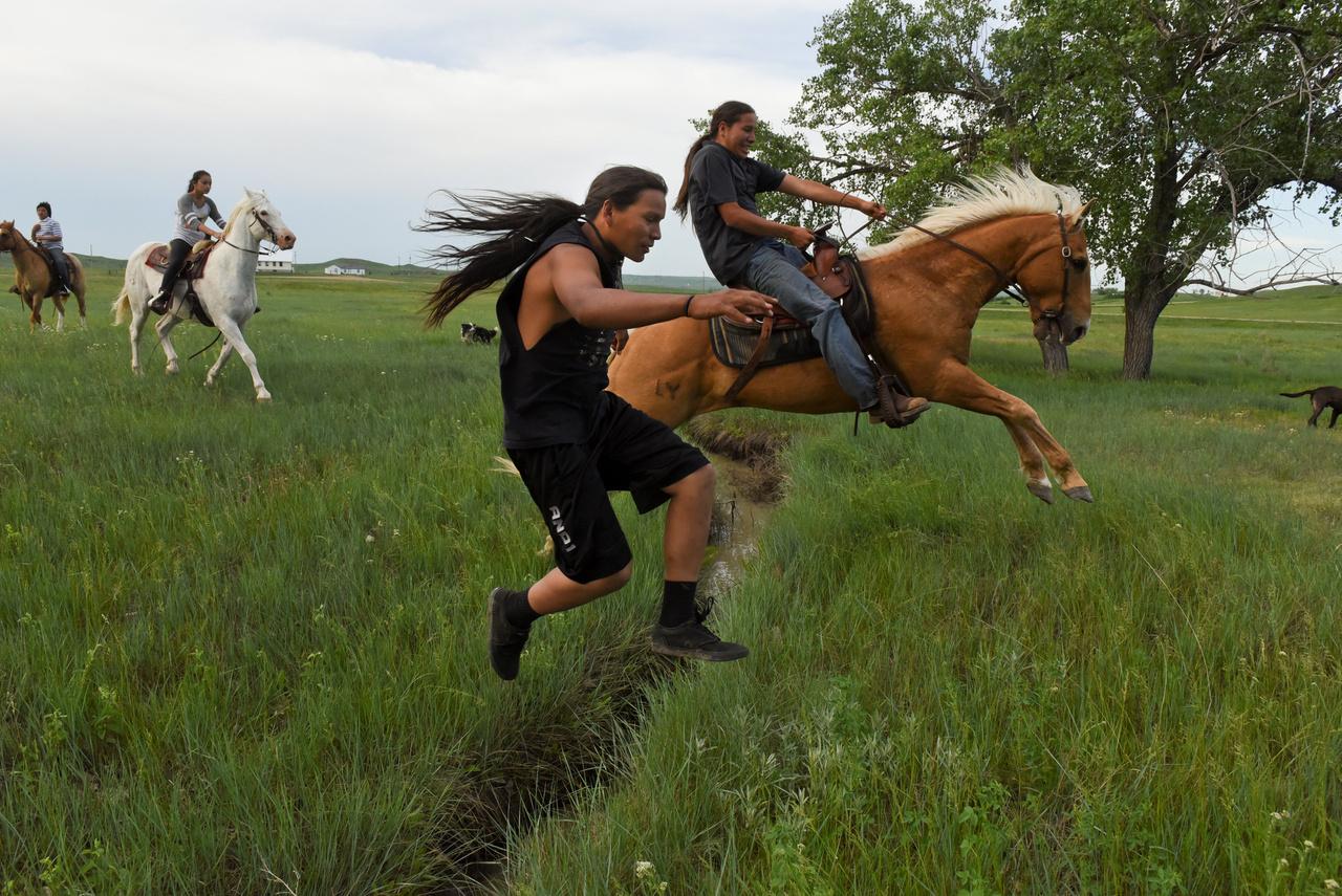 """Amikor a fehérek lovaikkal és puskáikkal meghódították azt a végtelen területet, amit Amerikának neveztek el, a föld eredeti lakóinak a lótartást sem akarták megengedni, azt mondták nekik, veszélyes vadállatok, ne merjenek a közelükbe menni. A sziú indiánok így hát égi adományként kapták a lovakat, melyek aztán népük egész életét meghatározták. A legenda szerint egy bátor fiú, """"Kis Kutya"""" a hegyekben egyedül vadászva népéért fohászkodott, amikor magas alak jelent meg egy csodálatos állat hátán. """"Ezt az állatot Szent Kutyának nevezik. Képes arra, amire a kutyáitok, és még azon kívül sok mindenre. Gyors mint a szélvész, nemes lény, de félelmetes is"""" - szólt az ismeretlen, majd a felhők összezáródtak, és számtalan Szent Kutya esett le az égből. A Nagy Szellem ajándékát a fiú hazavitte népének, akik így kapták meg a Szent Kutyát, vagyis a lovat."""