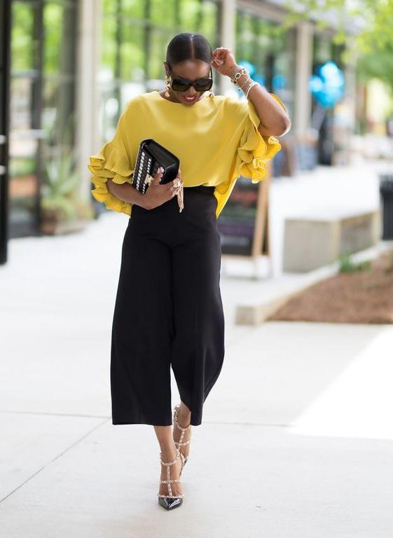 Egy elegáns, fekete culotte-nadrággal vagy egy midi szoknyával párosítva az irodába is tökéletes választás egy sárga felső. Feldobja a szettet, és a kontraszt miatt az összeállítás karcsúsít is.