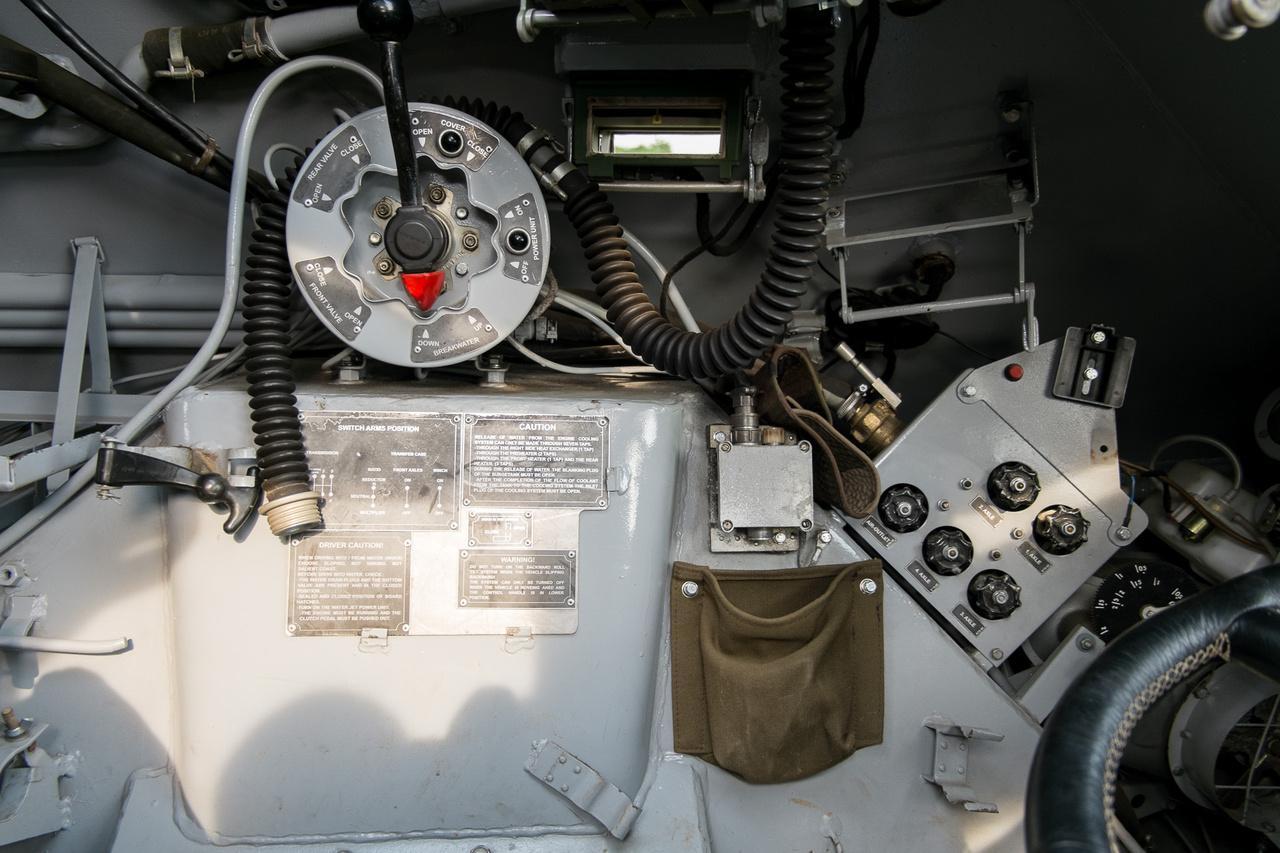 """A nagy, kerek dob, rajta a karral a """"BTR iDrive-ja, ahogy Peti találóan megjegyezte. Ebben a dobozban persze semmi elektronika nincs; ez egy pneumatikus vezérlődob, amelyen olyan dolgokat lehet aktiválni és alaphelyzetbe tenni, mint a jármű orrán a hullámtörő, a vizes hajtás, a légmentes lezárás. Kicsit előtte, lejjebb a sok vízcsapszerűség a kerekek felfújását vezérli."""