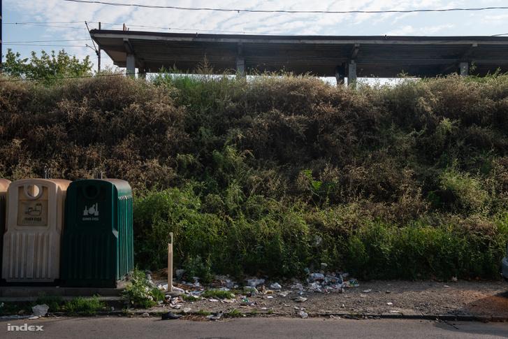 Szelektív hulladékgyűjtők mellé kiszórt szemét az állomás alatti töltés mentén.