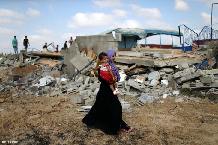 Palesztin nő viszi gyermekét korábbi izraeli légi csapás helyén, Khan Younisban Dél Gázai-övezetben, 2018.08.09.
