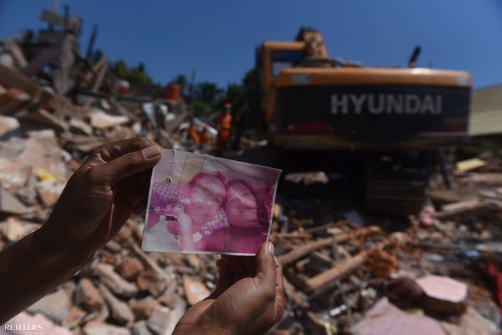 Helyi lakos mutatja hiányzó áldozatok képét, úgy hiszik az összeomlott épület alá szorultak. Mentők tovább folytatják a keresést a vasárnapi földrengés után Pemenangban, Észak-Lombokban.