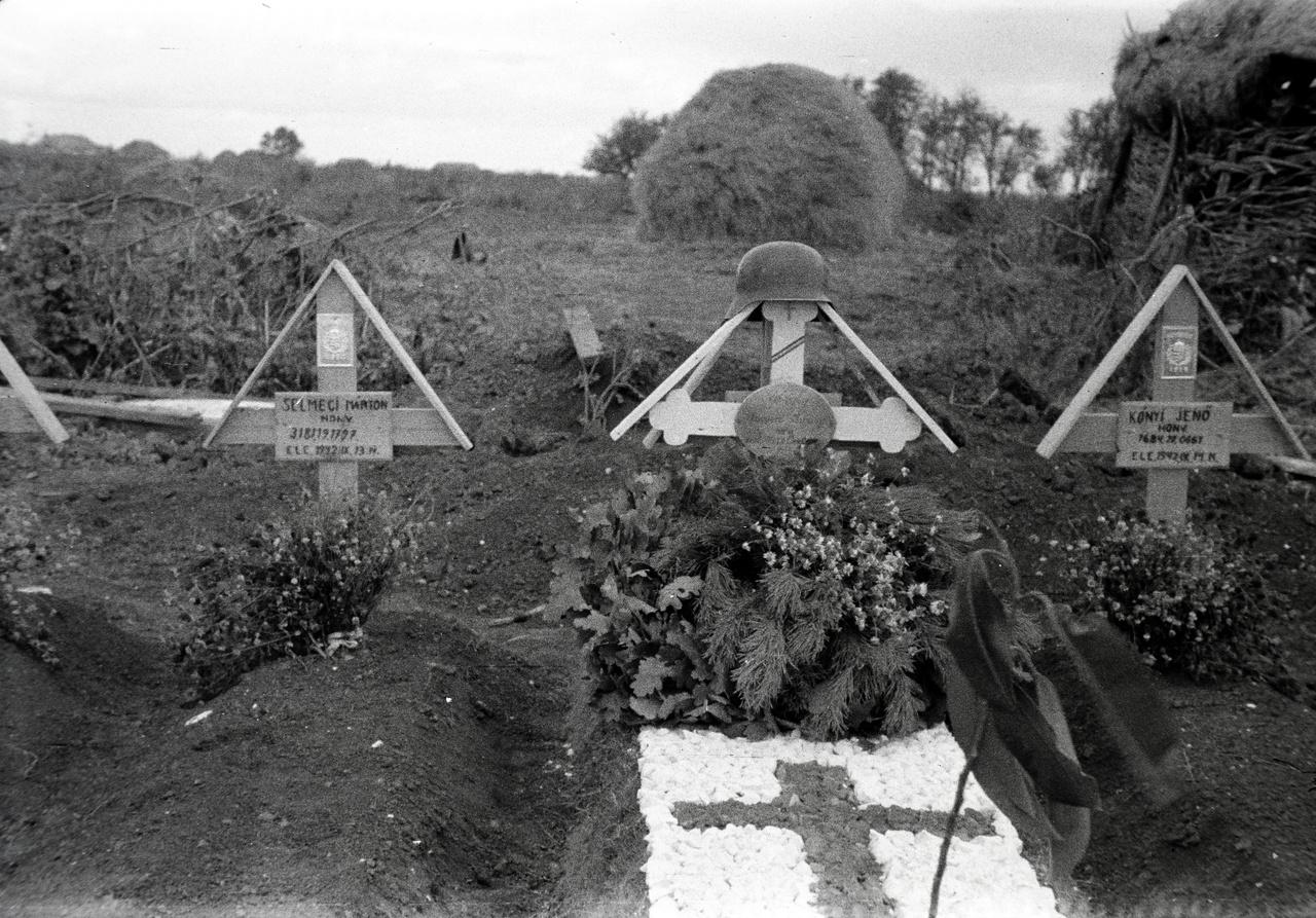 """Díszsír kavicsokból kirakott kereszttel, koszorúval az egyik (úgy tudjuk, ma már nem létező) oszkinoi temetőben. A 2. hadsereg egykori oroszországi hadműveleti területén, a Dontól 8 kilométerre fekvő Oszkino összesen három temetőjében az 1942 augusztusi és szeptemberi hídfőcsaták során elesett honvédek nyugodtak. Illetve az 1942 novembere és 1943 januárja között itt meghalt szombathelyi közmunkaszolgálatosok. A halálozás okai között a sebesülés mellett legtöbbször szívelégtelenség szerepelt, a zsidó közmunkaszolgálatosok között végkimerülés, öngyilkosság. A Béke poraikra idéz róluk egy korabeli harctudósítást: """"A zsidó kisegítő munkaszolgálatosok erőállapota egyenesen siralmas volt. Az utóbbi időben már alig akadt egy-két munkaképes egyén. A halálozás napirenden volt, úgyhogy kb. 200 fő halálozott el testi leromlás következtében."""""""
