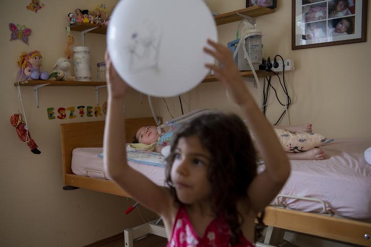 Bogi lufikat paszolgat Eszternek, aki már csak a szemével tudja követni a ballon mozgását