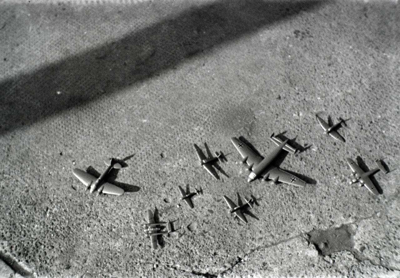"""Márta tizenöt éves szőke, göndör hajú és szép arcú unokatestvére bolondult a repülőgépekért és a hadi dolgokért. Mikor már a háború a végéhez közeledett, 1945 végén barátaival egyikük pincéjében elkezdtek mindenféle fegyverdarabokat gyűjtögetni. Ott lent ezeket megpróbálták összerakni, és mivel gyerekek voltak, elkezdtek velük játszani. Soha nem tudták meg, ki volt az, aki ekkor feljelentette a kamaszokat. Mikor a kommunisták eljöttek a fiúért, az egész lakást rettenetesen feldúlták. Élete a Katonapolitikai Osztály kezébe került, akiknek feladata a hírszerzés és elhárítás mellett a háborús és népellenes bűnösök felderítése volt. A fiút agyonverték, megkínozták, majd az  ÁVH központjába, az Andrássy út 60. alá került (a mai Terror Háza Múzeum). Statáriális bíróság elé állították, ahol koncepciós perben hat év börtönre ítélték. A vád: fel akart robbantani egy gyárat. A fiút csak azért nem akasztották fel, mert mindössze tizenöt éves volt.Márta nagyapja minden követ megmozgatott, hogy kihozza a fiút a börtönből, végül két évvel később sikerült őt kiszabadítani. A történtekről nem beszélhetett. Elvégezte a Népszínház utcában található Technológiát (későbbi nevén Felsőfokú Gépipari Technikumot), utána pedig három évre elvitték katonának.Az unokatestvér élete ezek után meghasonlott, a fiú visszahúzódó és introvertált lett, és egész életére rányomta a bélyegét az, amit fiatalon elszenvedett. Hiszen még az újságok is úgy írtak róla: """"Jólöltözött úri ficsúr akarta fölrobbantani a gyárat"""". A fenti fotón az ő gyerekkori hadi játékmodelljei vannak."""