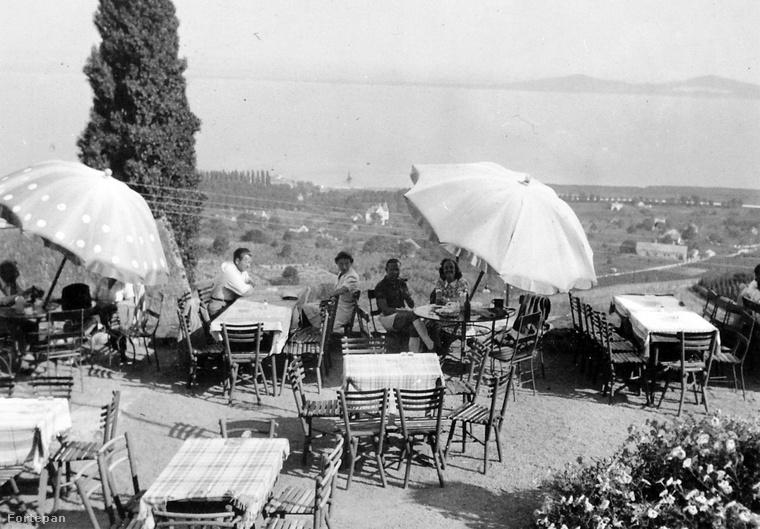 1940 nyarán, kockás terítő fölött, pöttyös napernyő alatt élvezik a csodás balatoni panorámát a turisták a badacsonyi Kisfaludy ház teraszán