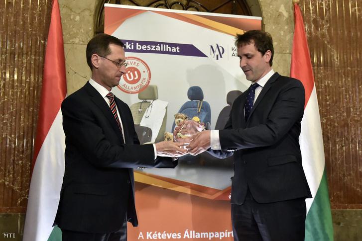 Varga Mihály miniszter (b) emlékplakettet ad át Barcza Györgynek az Államadósság Kezelő Központ (ÁKK) vezérigazgatójának az új kétéves futamidejű államkötvényt bejelentő sajtótájékoztatón a Nemzetgazdasági Minisztériumban 2017. április 3-án.