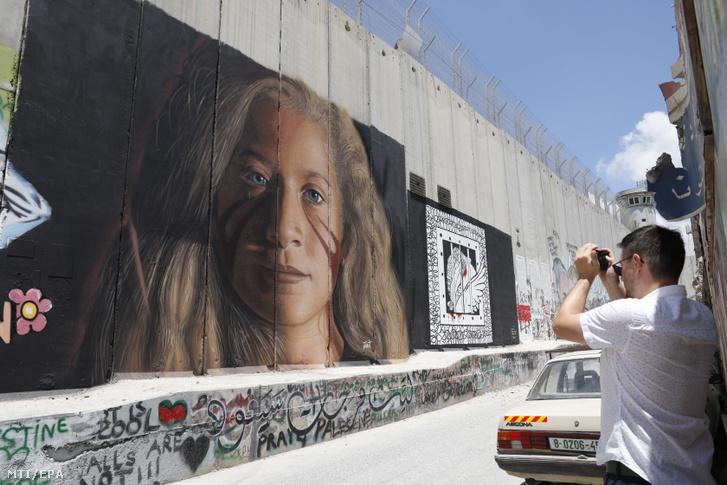 Ahed Tamími 17 éves palesztin lányt ábrázoló, Jorit Agoch olasz művész által az Izraelt a palesztin területektől elválasztó védőfalra készített festményt fényképezi egy turista a ciszjordániai Betlehemben 2018. július 29-én.