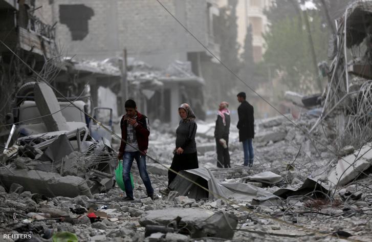 Emberek a lebombázott házak között Afrinban 2018. március 24-én