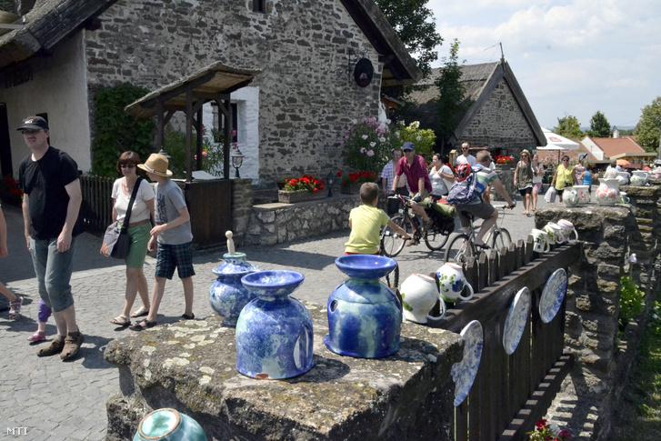 Turisták sétálnak a település központjában a Pisky sétány népmûvészeti termékeket kínáló üzletei elõtt.