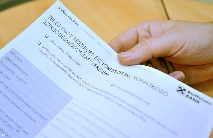 A végtörlesztéshez szükséges nyomtatványt nyújtja át egy alkalmazott az ügyfélnek a Raiffeisen Bank budapesti székházában 2011-ben.