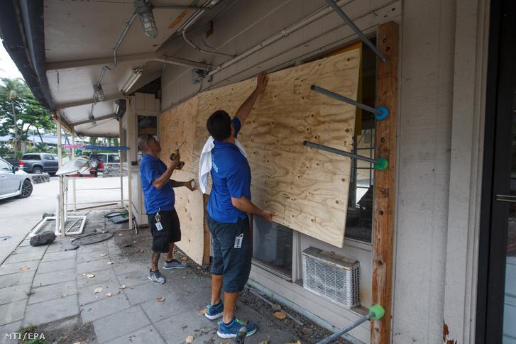 Munkások bedeszkázzák a Kona Seaside szálloda ablakait a Hawaii szigetén lévő Kailua-Konában 2018. augusztus 22-én, a Lane hurrikán érkezése előtt.