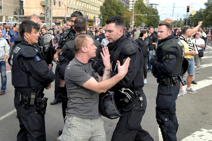 Szélsõjobboldali tüntetõ rendõrrel dulakodik a kelet-németországi Chemnitzben két nappal ezelõtt történt gyilkosság miatti tiltakozáson 2018. augusztus 27-én.