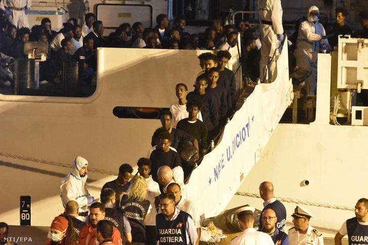 Menekültek partra szállnak az olasz parti õrség Diciotti hajójának fedélzetérõl Catania kikötõjében 2018. augusztus 26-án.
