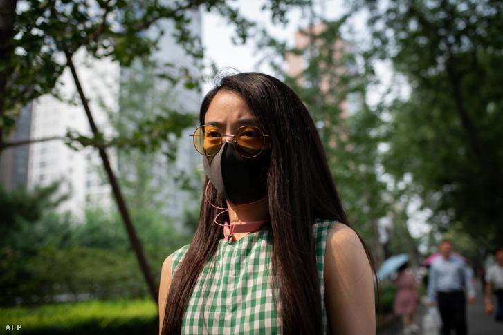 Egy nő maszkot visel az erősen szennyezett levegőjű Pekingben