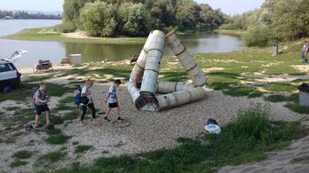 Olajoshordó-szobor és a felcímkézett uszadékfák a Duna-parton