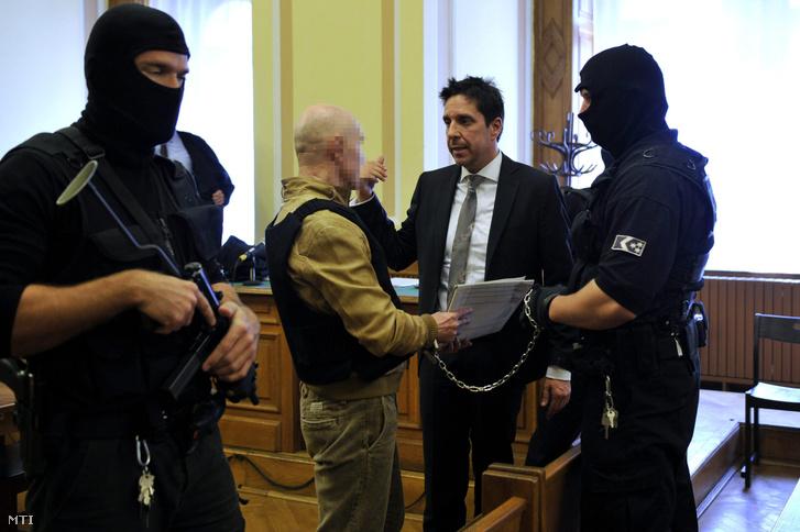Jozef R. (b2) ügyvédjével Fülöp Tamással beszélget büntetőperének tárgyalásán a Fővárosi Törvényszék tárgyalótermében 2014. április 3-án