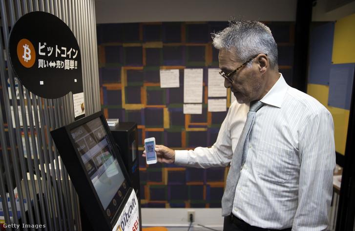 Egy munkavállaló okostelefonnal Bitcoint vásárol egy bitcoin automata eladó gépen a Coint Trader kiskereskedelmi üzletében Tokióban