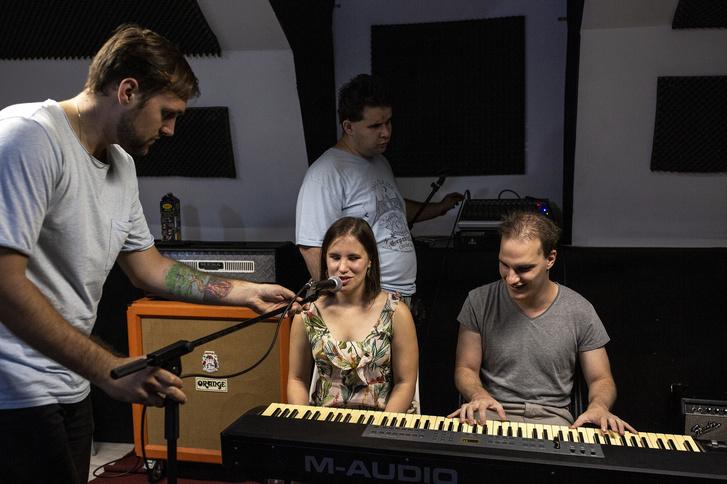 Máté segít összeszerelni a hangszereket. / A képen Máté állítja Annamáriának a mikrofont, mellette Maximilian zongorázik, a háttérben István a hangtechnikát állítja.