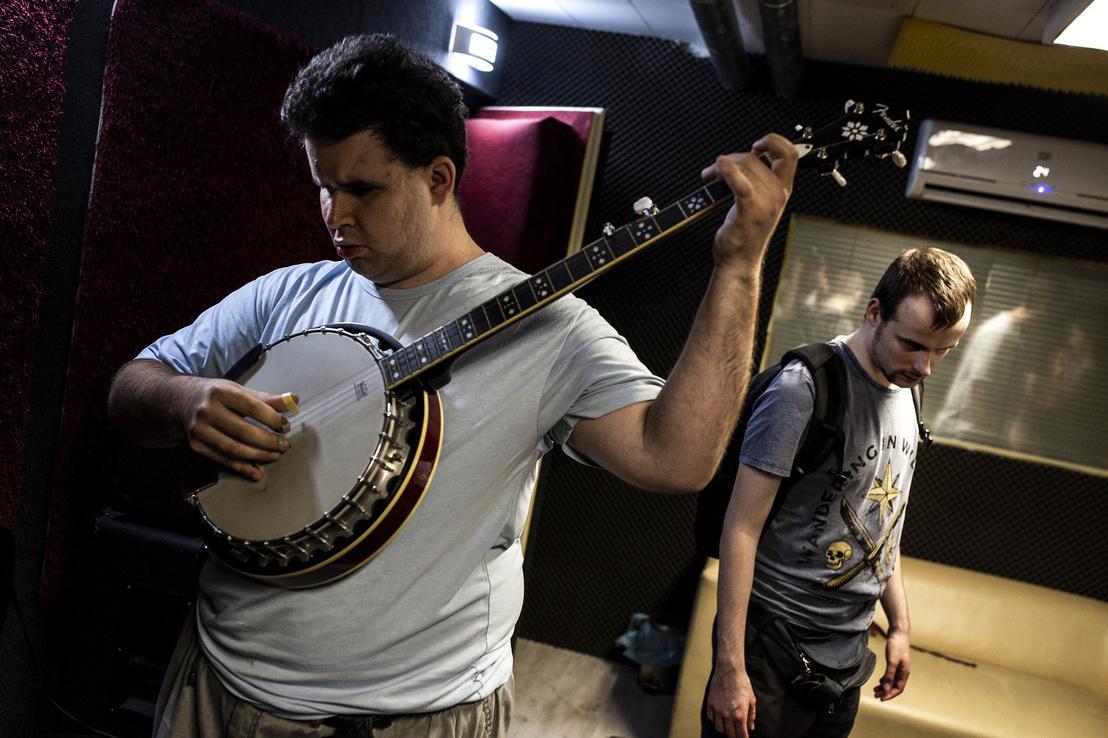 István basszusgitáron is játszik./ A kép előterében István bendzsón játszik, a háttérben László áll táskával a hátán.