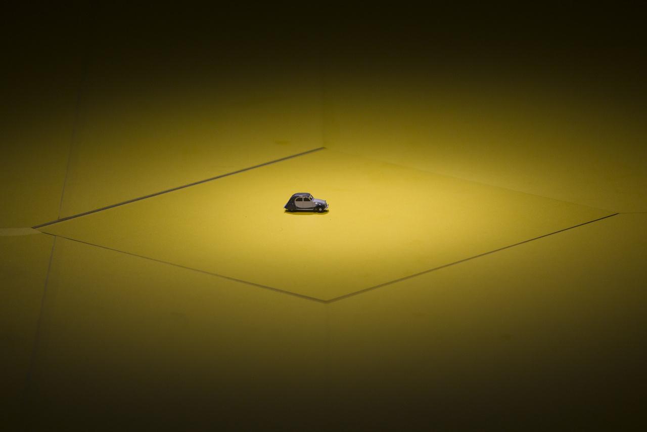Aranyos geg a kiállításon: az egyik pódiumot egy aprócska modellautó foglalja el, egyfelől a játékipar, másfelől a modellgyűjtők felé biccentve kicsit.