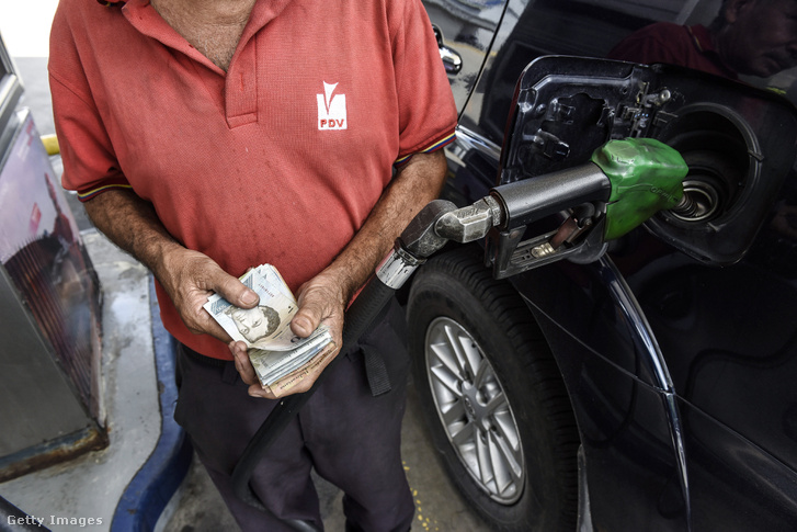 Benzinkutas Bolivar bankjegyeket tart a kezében a Petroleos de Venezuela SA (PDVSA) benzinkúton Caracas, Venezuela, 2018.09.03.
