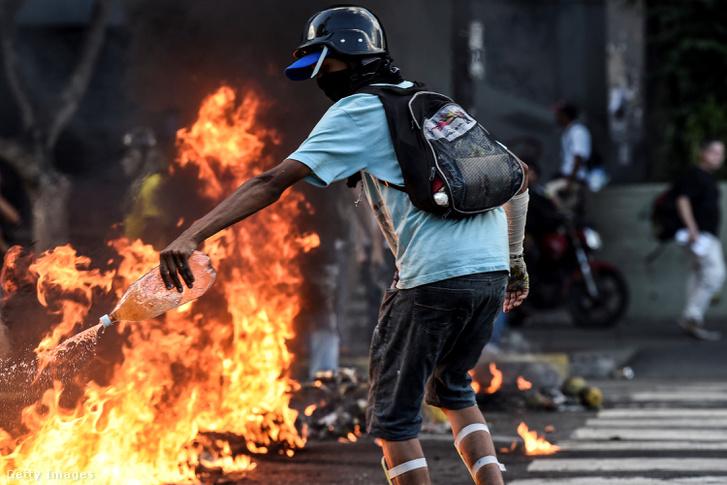 Maszkos tüntető benzint ön a lángokra Nicolas Maduro elnök kormánya elleni tiltakozáson. Caracas, Venezuela, 2017.05.20.