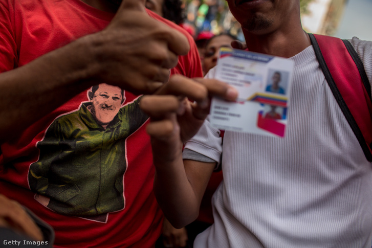 """Egy tüntető Hugo Chavezes pólóban mutatja a """"Carnet de la Patria"""" szülőföld kártyáját, a venezuelai kormány melletti megmozduláson. Caracas, Venezuela 2018.08.21."""