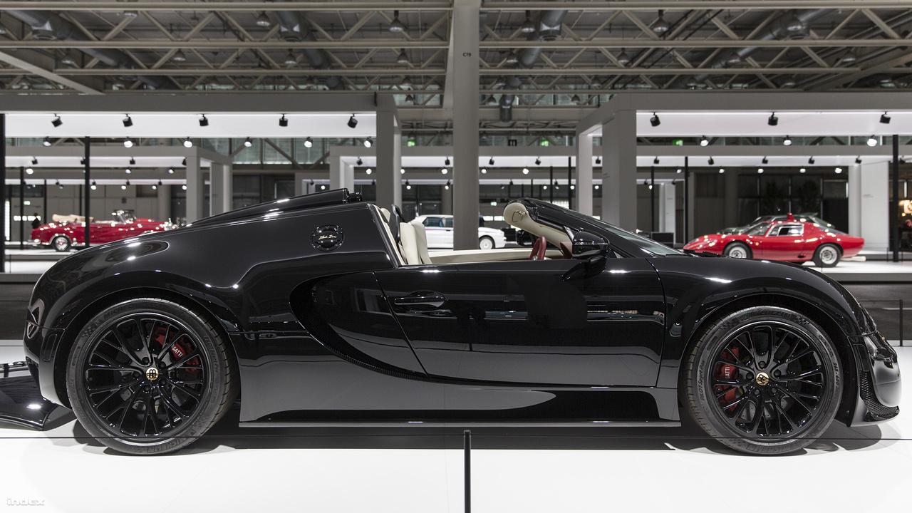 """Bugatti Veyron Grand Sport Vitesse, """"Black Bess"""", 2013. 2005-ben sokkolta a világot a Bugatti Veyron. Soha előtte nem volt olyan kereskedelmi forgalomban kapható, sorozatgyártott utcai autó, ami több mint ezer lóerős motorjával több mint 400 km/órás sebességre lett volna képes. Az 1001 lóerős, (finoman szólva) bizarr megjelnésű Veyron 408-cal is képes száguldani, miközben 2,5 mp alatt van százon. A képen látható éjfekete, részben 24 karátos arannyal bevont alaktrészeket tartalmazó példányt a 2014-as pekingi autóshow-n mutatta be a német-francia gyártó, egy hatrészes Bugatti-legendék sorozat tagjaként. Összesen három darab készült belőle."""