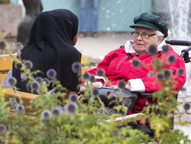 Fiatal afrikai bevándorló nő egy öreg helybeli asszonnyal beszélget Flenben
