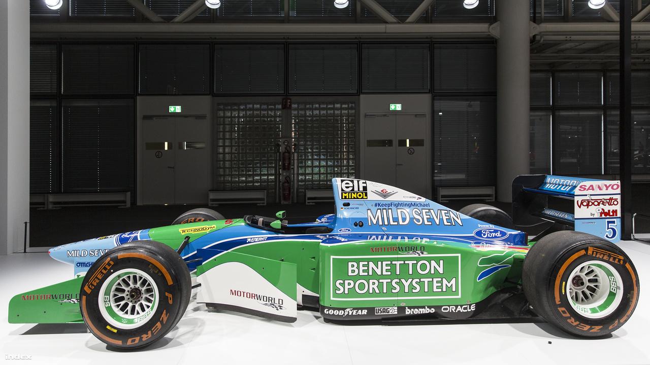 Benetton B194-05, 1994.                          Benetton Ford B194-05, 1994. A Forma-1-es autóversenyzés egyik legdrámaibb évében, 1994. május 1-jén a San Marino-i verseny közben életét veszti a sportág, egyben minden idők legnagyszerűbb autóversenyzője, a brazil Ayrton Senna. Ugyanebben az évben azonban új csillag is született: a német Michael Schumacher a fenti Benetton versenyautóval megszerezte élete első világbajnoki címét, amit még hat követett kivételesen sikeres versenyzői pályafutása alatt. Az autón olvasható #KeepFightingMichael hashteg a 2013-as súlyos síbalesete óta a felépülésért küzdő Schumachernek szurkol.